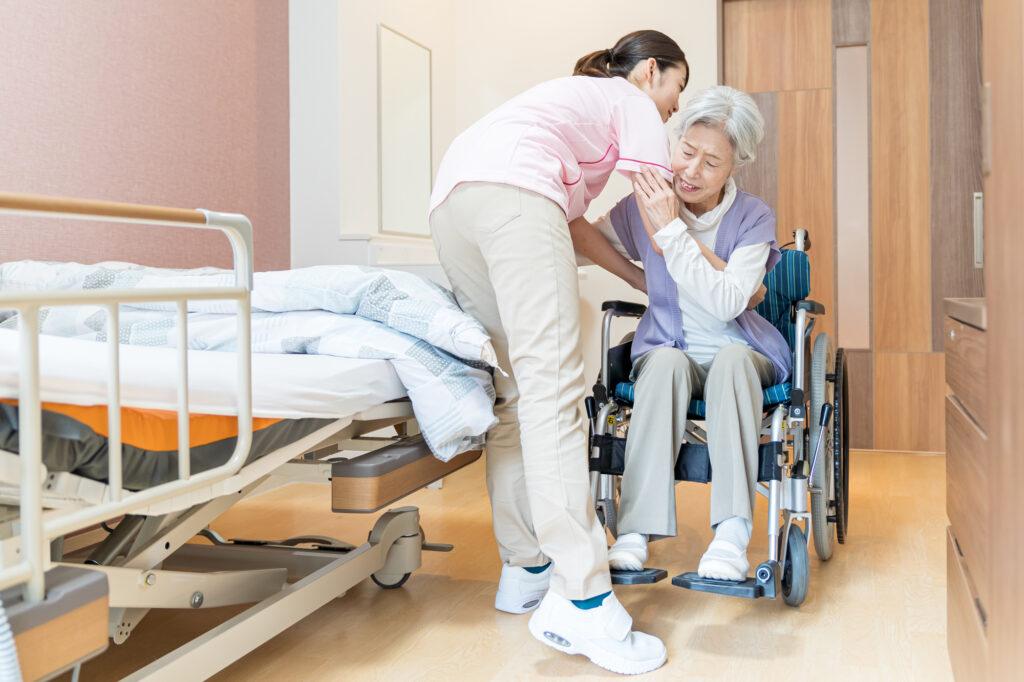 車いすから移乗する女性介護士