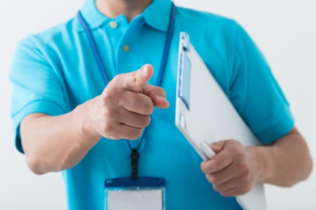 指を指す男性介護職員