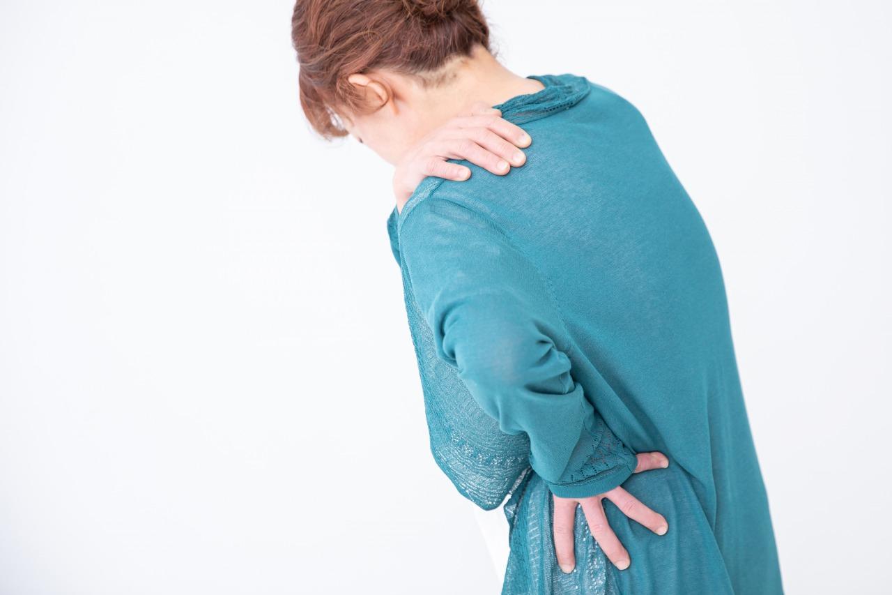 運動不足で体を痛めている女性